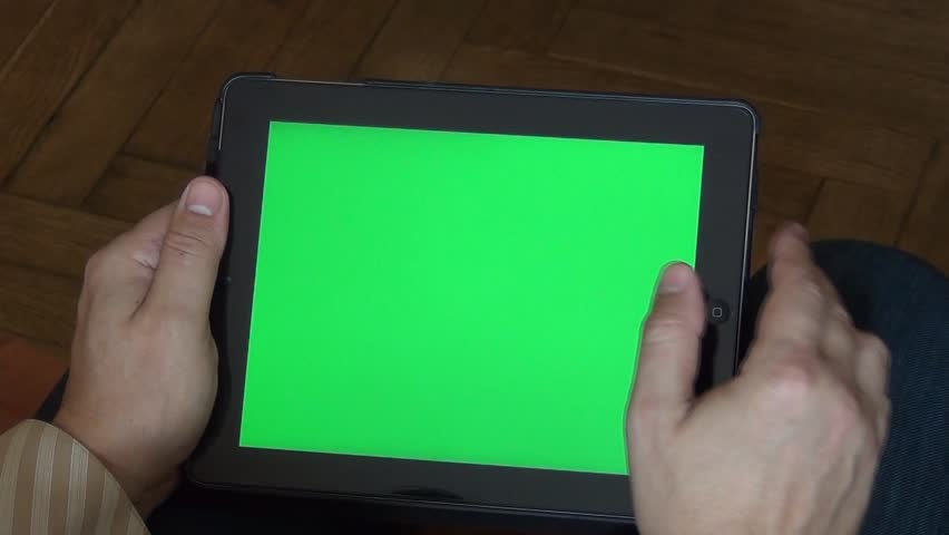 Man holds tablet PC with green screen. Chroma key screen for placement of your own content.
