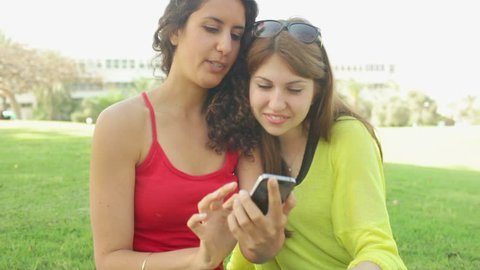 Two girls laughing at something on the screen of the phone