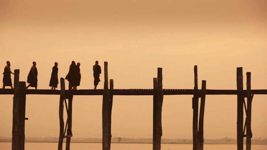 A group of Buddhist monks pass another monk, who playfully kicks one of them, at sunset on U Bein Bridge, the longest teak bridge in the world / Mandalay, Myanmar