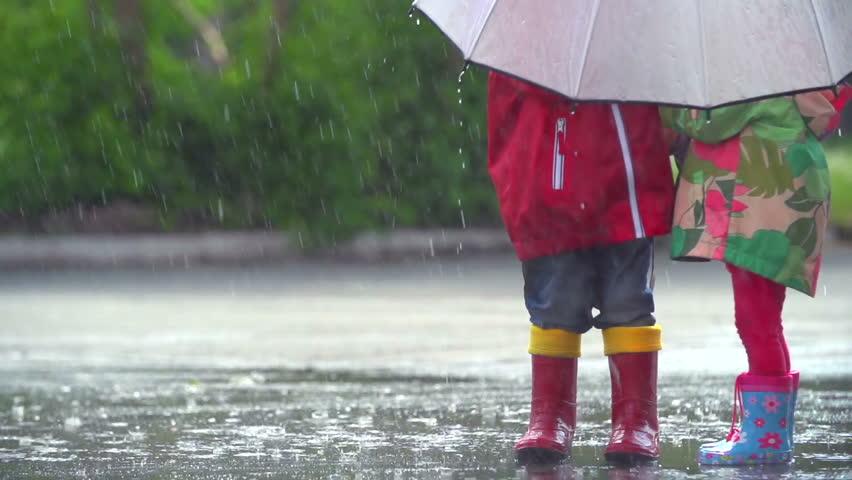 Kids hiding away from storm under umbrella
