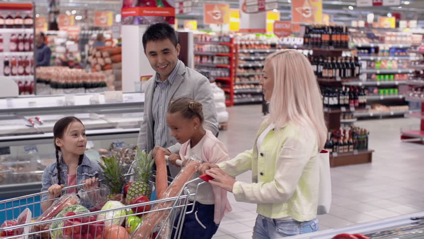 Tracking shot of family of four walking along supermarket rows with shopping cart in slow motion | Shutterstock HD Video #6823678