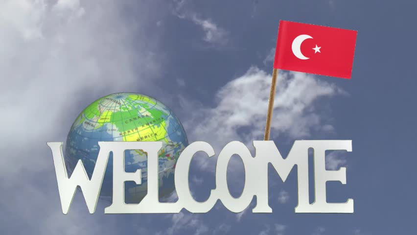 The word WELCOME in front of a turning globe and moving clouds in a blue sky with tooth pick and a small paper flag of TURKEY | Shutterstock HD Video #6848533