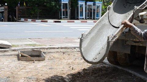 Construction workers pour concrete mix from cement mixer.
