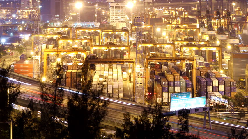 Cargo Container Loading Activity. Timelapse at night. Wide shot. Slowly zooming in. Busy traffice on highway at the front.      Shutterstock HD Video #690397