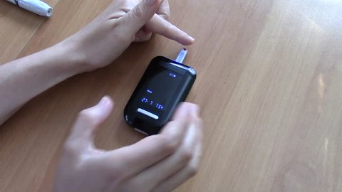Woman performs home glucometer