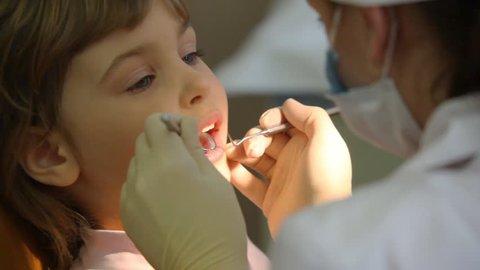 female dentist treats teeth of little girl