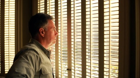Afternoon sunlight pours in the shuttered windows on to a man who is gazing solemnly through them.