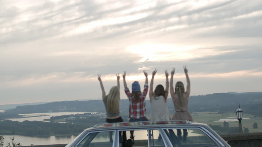 4 Teenagers Sit On Roof Of Car, Hold Up Peace Signs, Then Put Arms Around Each Other