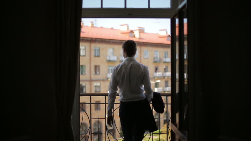 Silhouette of a man wears a jacket standing on the balcony of the hotel