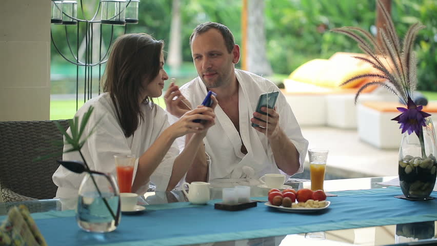 Couple Listen Music On Smartphone By The Table In Luxury Villa