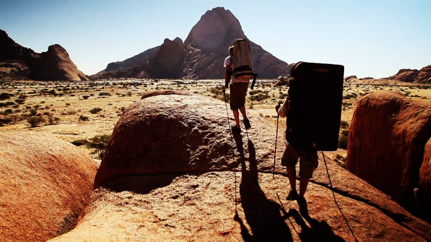 Two climbers with crash pads on their backs walk in beautiful landscape