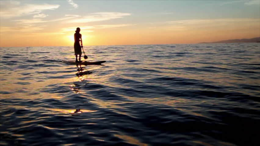 A man on a stand up paddle board during sunset