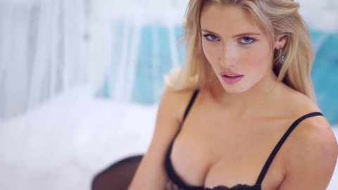 Beautiful seductive woman flirting with the camera sitting on a bed in black lingerie looking up with a coquettish look