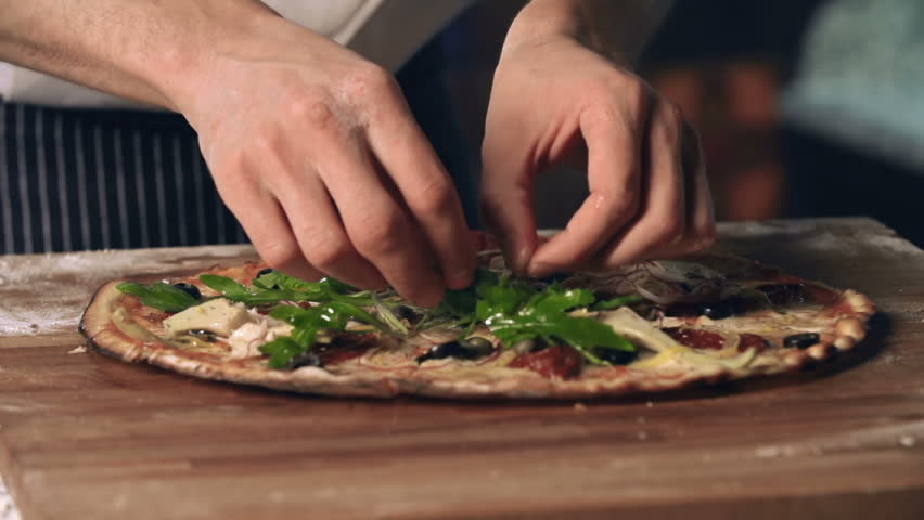 Close up of basil adding to pizza as a final touch to the dish