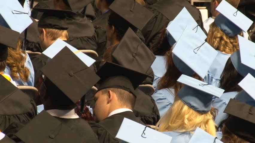 High angle shot from behind seated graduates during indoor ceremony.
