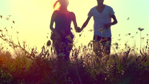 Happy couple having fun outdoors. Couple running away on the meadow. Countryside. Young Man and woman holding hands and running through a field with wild flowers. Sun flare. Slow motion 240fps HD 1080