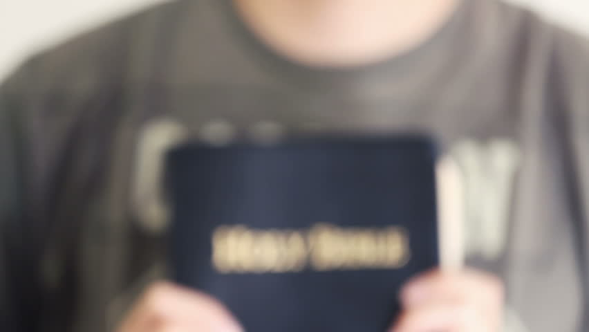young man proudly holding out his Bible
