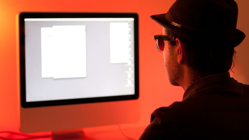 Time lapse of a young man in front of a computer on a color-full background