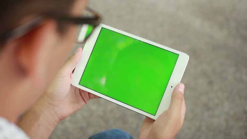 Young Man Holding Tablet Computer With Green Screen Chroma Key For Screen Replacement