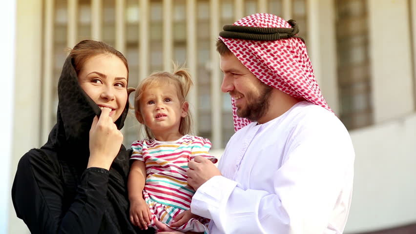 Portrait of a young couple in Arab robes with a small child in her arms. Arab family in the background of the city. Happy Arab family smiling at the camera. Young parents with a child.