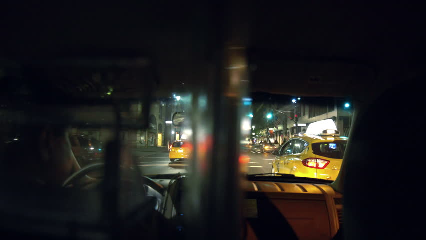 NEW YORK - AUGUST 9, 2014: Taxi cab interior driving from backseat at night in 4K in New York. Taxicabs can pick up passengers in any of the five NYC boroughs for transportation. | Shutterstock HD Video #7218985