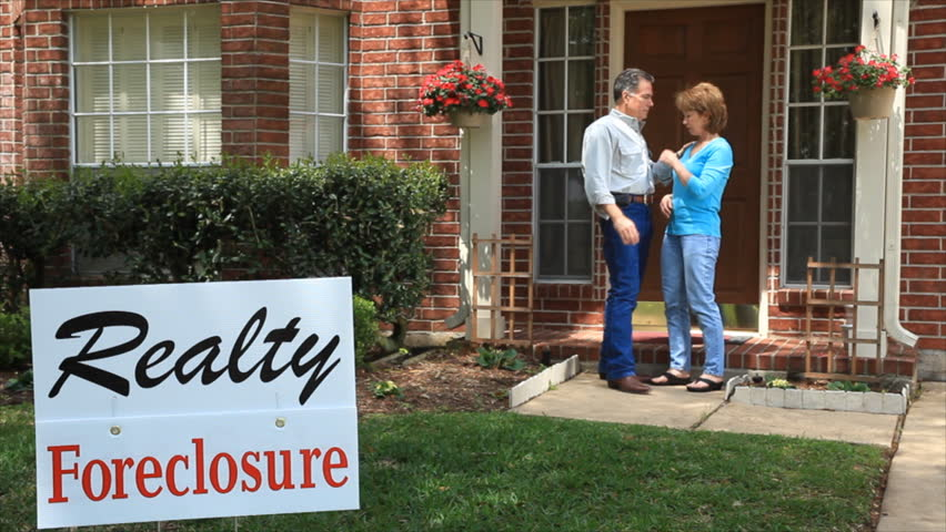 A man tries to console his wife who is distressed over the foreclosure sign in the front yard.