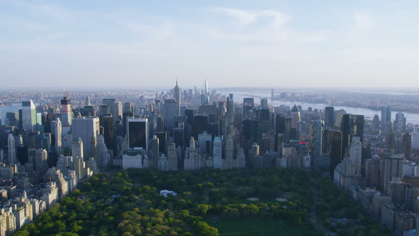 Aerial view of Central Park in New York City, United States of America. Helicopter flying over the green area of NYC. Sunset over iconic scene.