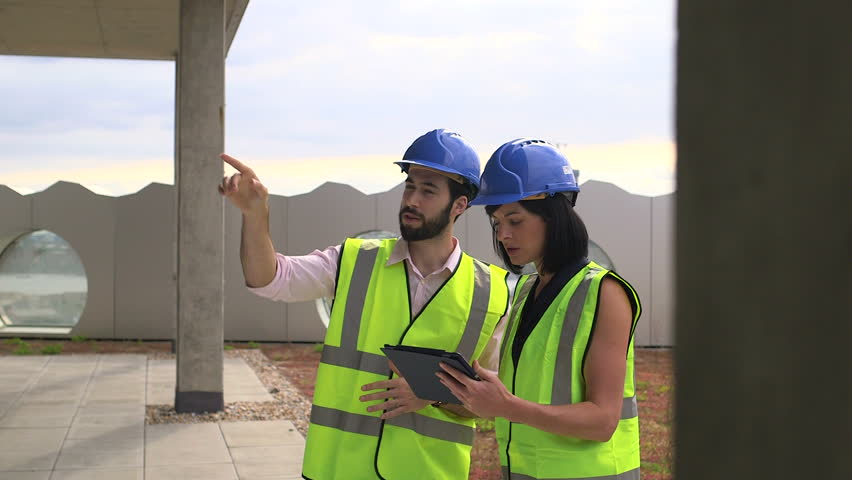 Man and woman discussing with digital tablet at construction site #7245433