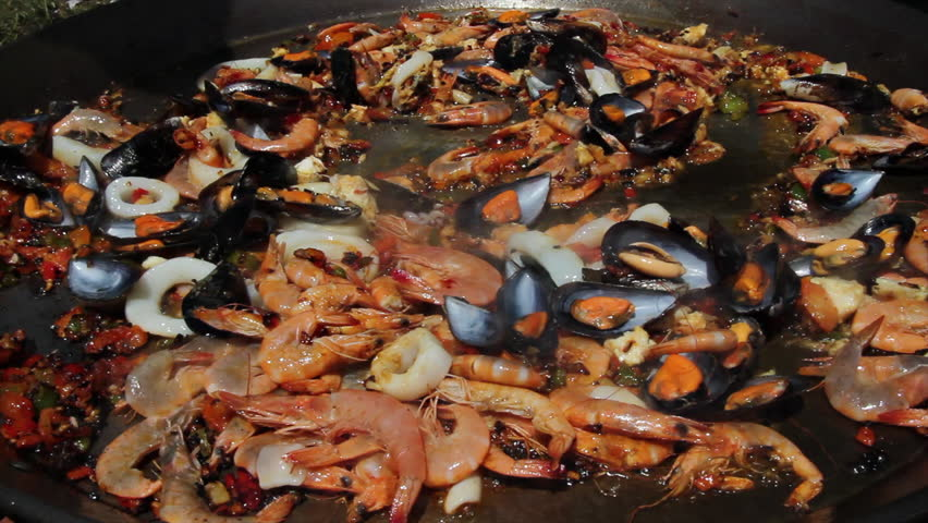 Frying the Ingredients of Paella - Stirring with a spoon a sauce with the basic ingredients for preparing seafood paella outdoors | Shutterstock HD Video #7248703