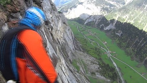Two person in wingsuits jump off the cliff and fly near to each other.