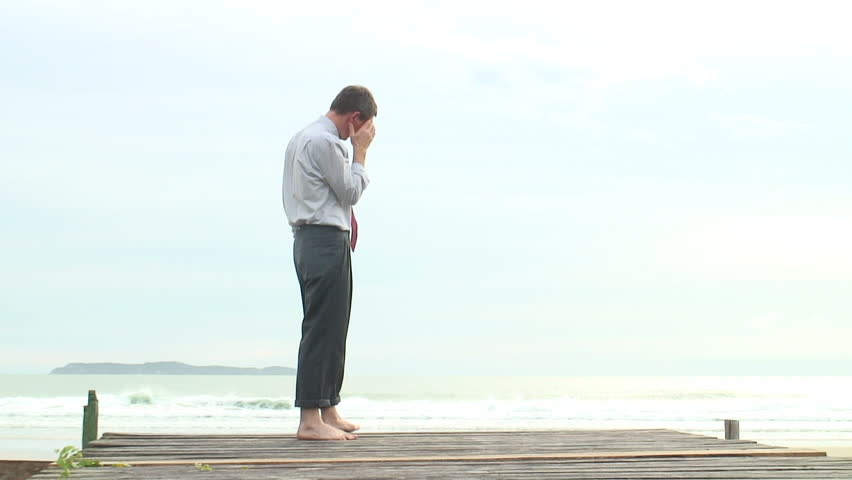 HD 1080i: Depressed barefoot businessman walking at the sea.