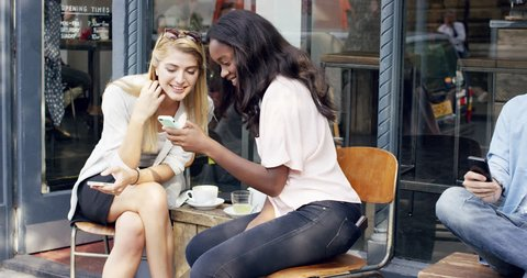 Female friends sharing together using smartphone in urban cafe