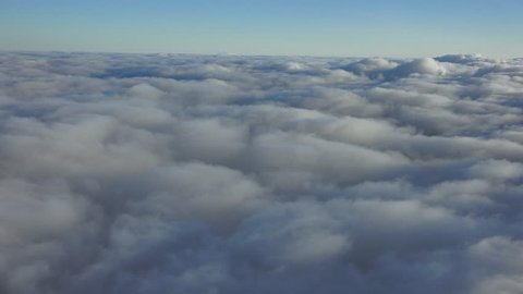 Aerial cloud deck, mid and low light skim down along cloud layers, in high end 4k res.