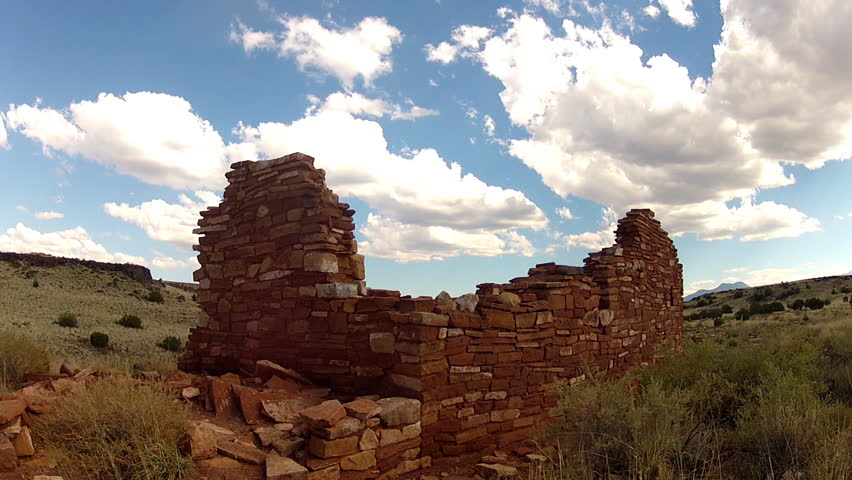 FLAGSTAFF, AZ/USA: July 12, 2014- A time lapse shot of big puffy clouds drifting over the ruins of an ancient Native American pueblo on the high desert plateau of Arizona circa 2014 near Flagstaff.