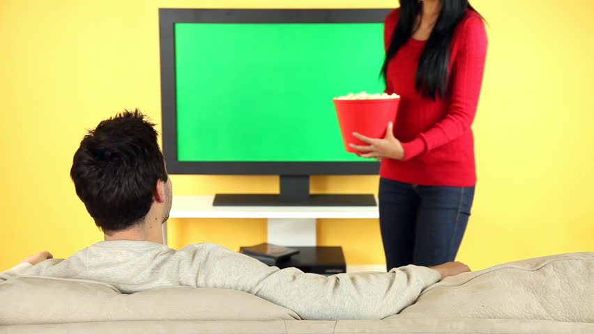 A young couple sitting on the sofa watching television and eating popcorn. TV screen is chroma keyed for adding your own movie or video. #7410385