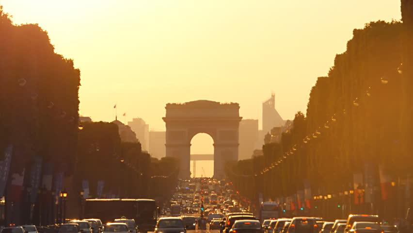 PARIS - JULY 1, 2014: traffic jam champs elysees avenue paris france at the sunset arc de triomphe warm color people come back from work