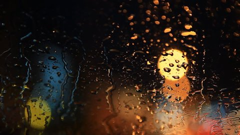 rain flows on the front windshield glass window of car stopping beside the road with beautiful colorful blurry light of traffic outside on the road, broken heart, sad, cry scene
