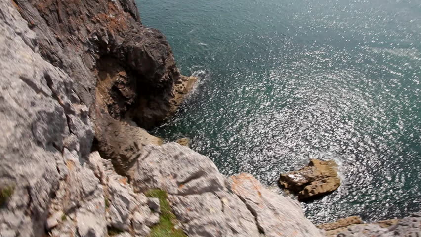 A rock climber climbs up a steep rock above the ocean, view from above