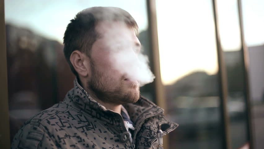 Bearded man smoking electronic cigarette. Medium profile shot.