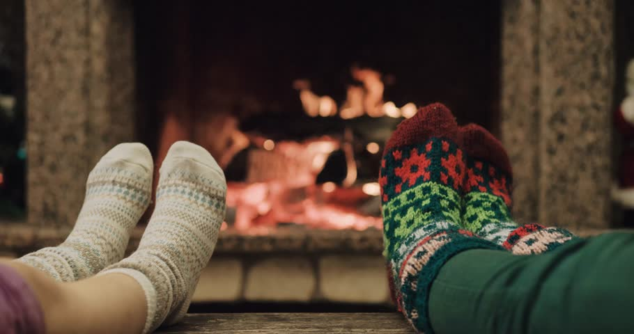 Feet in woollen socks warming by cozy fire in Christmas time in slow motion. Mother and child warming their feet by the fireplace in winter time. Filmed at 120 fps 4k graded from RAW