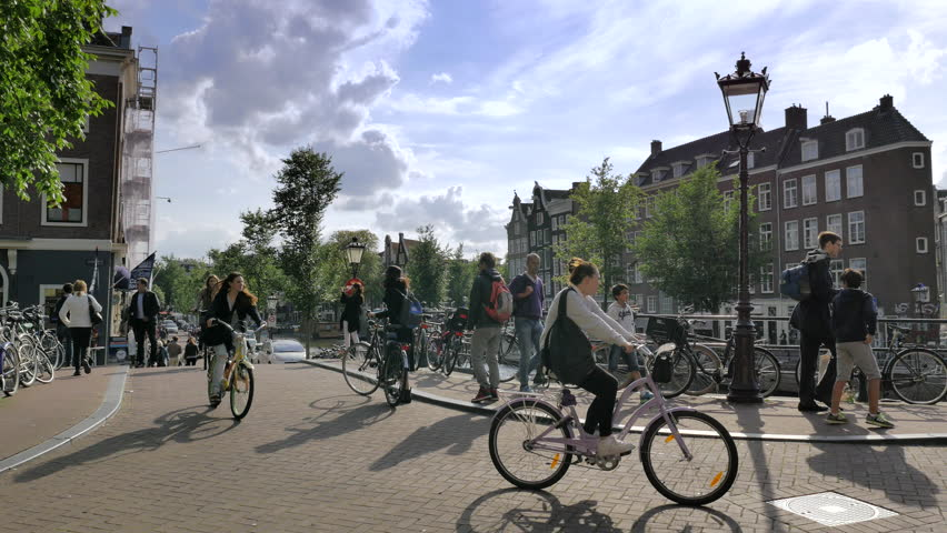 AMSTERDAM - AUGUST 21: Commuters on bikes in the central area of Amsterdam on August 21, 2014. Amsterdam is the most bicycle-friendly capital city in the world.