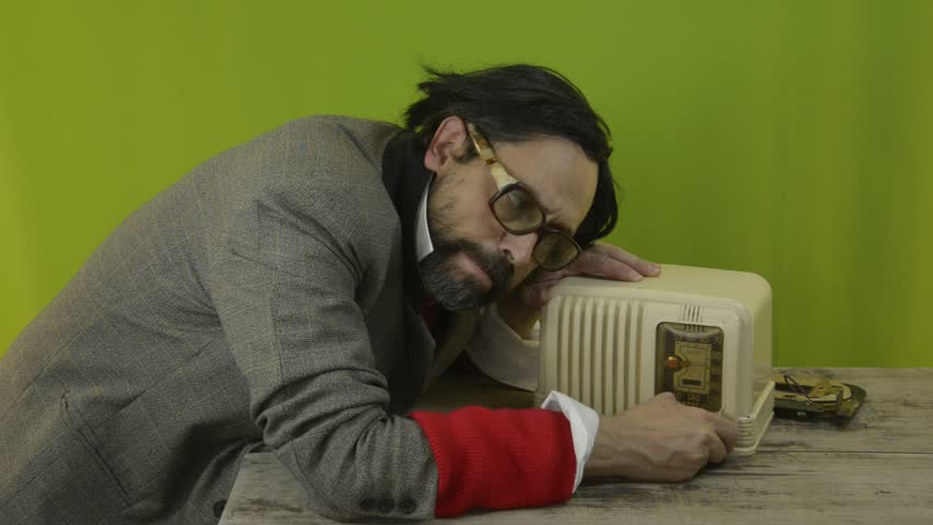 An untidy bizarre man, wearing big patched glasses and a toupee, trying to tune in a station on an old tube bakelite radio, over green background