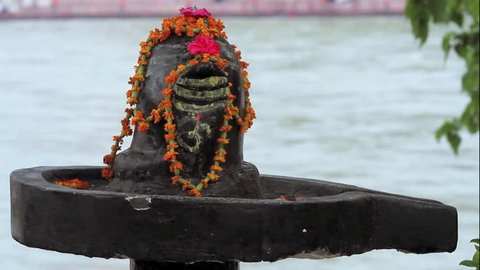 A close up shot of a Shiva-lingam, the generative symbol of the Hindu god Shiva with the Ganges River flowing in the background