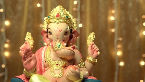 Ganesha- a statue of an Indian god against blinking christmas lights. Studio shot.