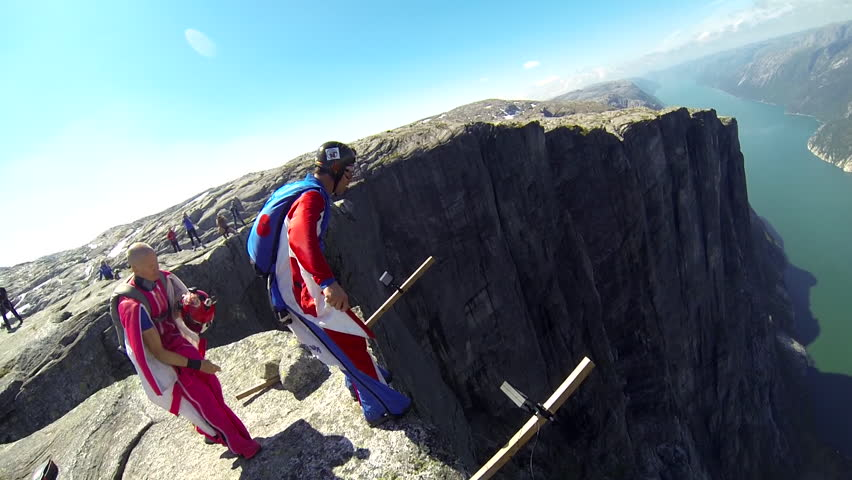 A base jumper jumps down from a cliff before gliding down in the air, a river visible below, POV