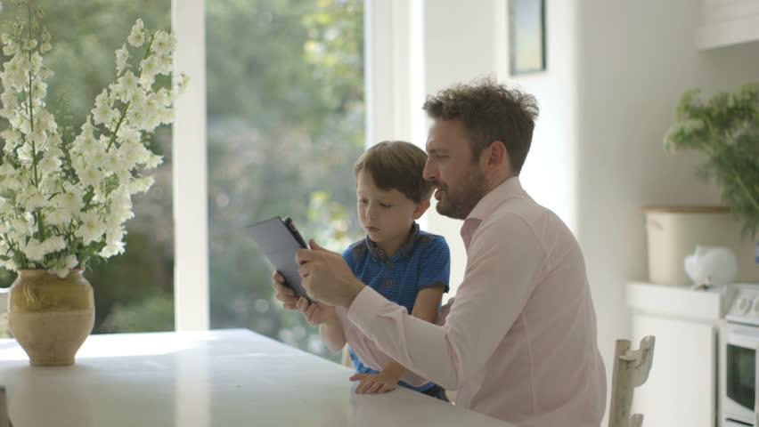 Father and son using digital tablet in domestic room   Shutterstock HD Video #7480642