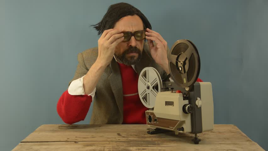 An untidy bizarre man, wearing big patched glasses and a toupee, projecting a movie with an old super 8 projector.
