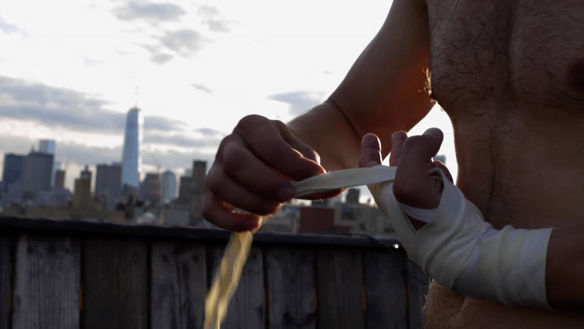 Boxer Wraps Hands on Rooftop with Manhattan Skyline in New York City - Wrapping Hands for Boxing Gloves with NYC in Background, Preparing for Fight