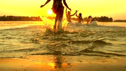 Group of happy girls running and playing in water at the beach on sunset. Beauty and joyful teenager friends having fun, dancing, spraying over summer sunset. Beach party. Sun flare. Slow motion 1080