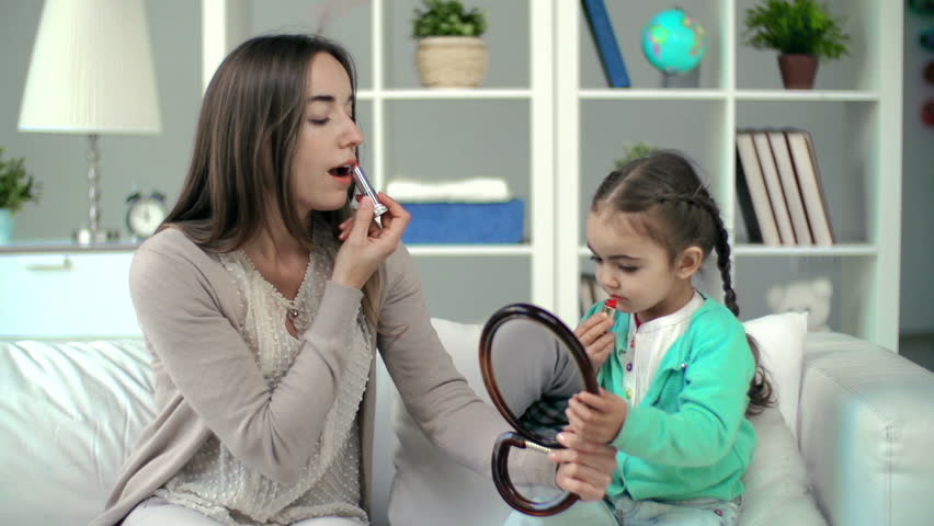 Mother showing daughter lipstick applying technique, girl failing to rouge correctly but having lots of fun